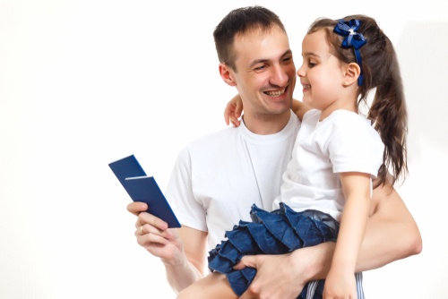 A father holding his daughter, his and a child passport.